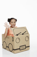 Girl sitting in a cardboard bus waving at the camera