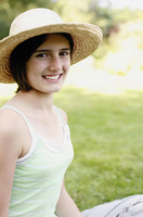Girl with a hat smiling at the camera