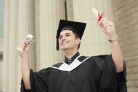 Graduate holding up his trophy and scroll