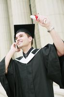 Graduate talking on the phone while holding up his scroll
