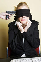 Gun being pointed at a blindfolded businesswoman