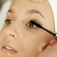 Hand curling up woman's eyelash with a mascara wand