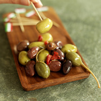 Hand taking fresh italian olive with italian flag pick from wooden plate