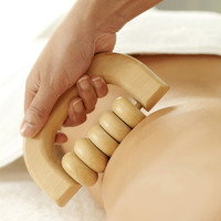 Hand using a wooden massager on woman's back