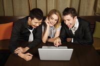 Happy business people looking at laptop