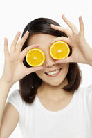 Happy woman covering both her eyes with an orange
