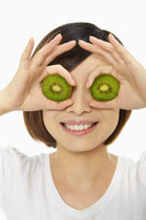Happy woman covering her eyes with a kiwi