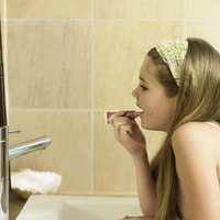 Little girl applying lip gloss in bathroom