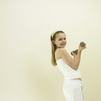 Little girl lifting dumbbell