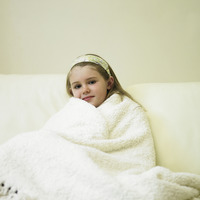 Little girl wrapped in blanket sitting on couch