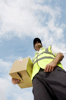 Low angle view of a delivery man carrying a box