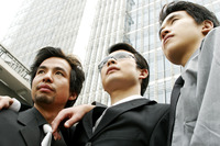 Low angle view of three businessmen standing in front of the building