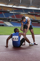 Male athlete laying on track, clasping leg in pain, another athlete helping