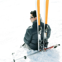 Male skier sitting with his skis and ski poles
