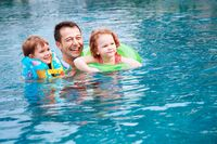 Man and children swimming in the pool