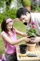 Man and girl planting flower into flower pot