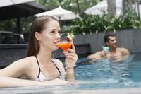 Man and woman drinking while relaxing in the pool