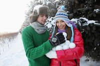 Man and woman gathering an armful of snowballs