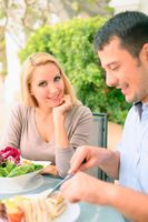 Man and woman having a meal at an outdoor restaurant