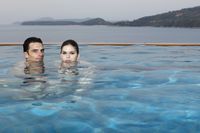 Man and woman in pool, heads half submerged in water