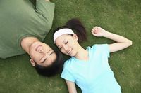 Man and woman lying on the field, eyes closed