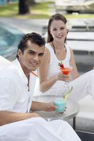 Man and woman on lounge chairs with their drinks