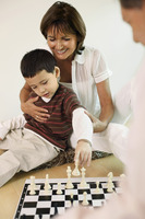 Man and woman playing chess game with boy