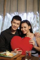 Man and woman posing with heart-shaped cushion