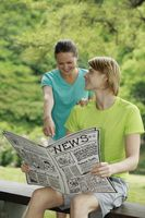 Man and woman reading newspaper together