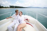 Man and woman resting on speedboat