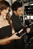 Man and woman selecting wine bottles from rack
