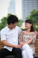Man and woman sitting on a bench, smiling