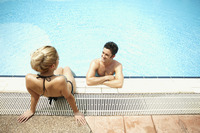 Man and woman talking while relaxing by the poolside