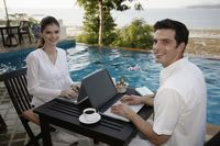 Man and woman using laptop by the pool side