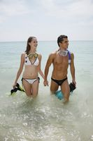 Man and woman with snorkeling gear on beach
