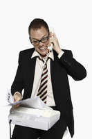 Man answering phone call while getting bills from fax machine