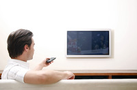 Man controlling television with a remote control