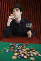 Man drinking wine and smoking cigar at gaming table