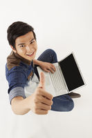 Man giving thumbs up while using laptop