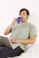 Man having a drink while using laptop