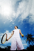 Man holding tennis racquet and ball