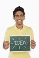 Man holding up a blackboard with an 'idea' word on it