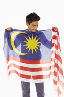 Man holding up a malaysian flag