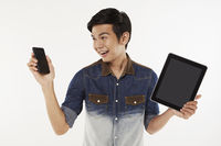 Man holding up a mobile phone and digital tablet