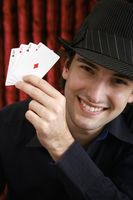 Man holding up four aces in casino