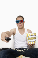 Man in 3d glasses watching television and holding popcorn