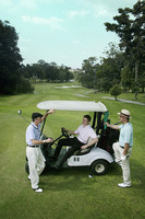 Man in a golf cart with his friends around him