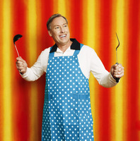 Man in apron holding a ladle and a spatula