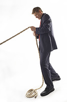 Man in business suit pulling a rope with all his might