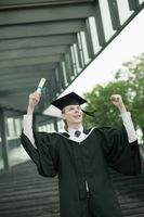 Man in graduation gown holding up his scroll